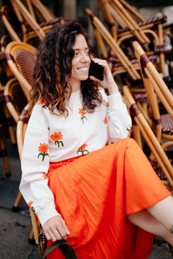 Femme portant une jupe midi taille élastique orange upcyclé réalisé par nos couturières le téléphone à la main