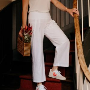 Femme portant un pantalon à plis blanc upcylé réalisé par nos couturières