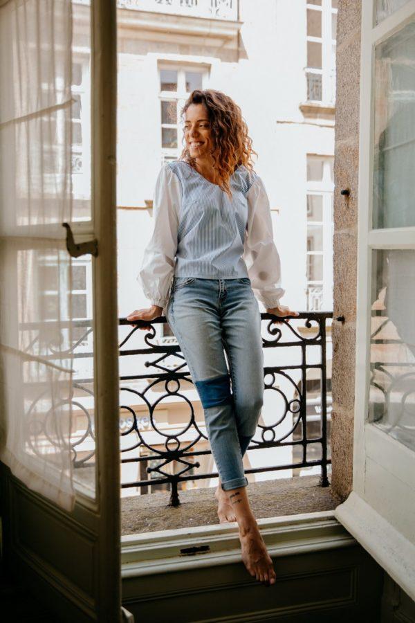 Femme portant un haut bleu et blanc upcyclé réalisé par nos couturières