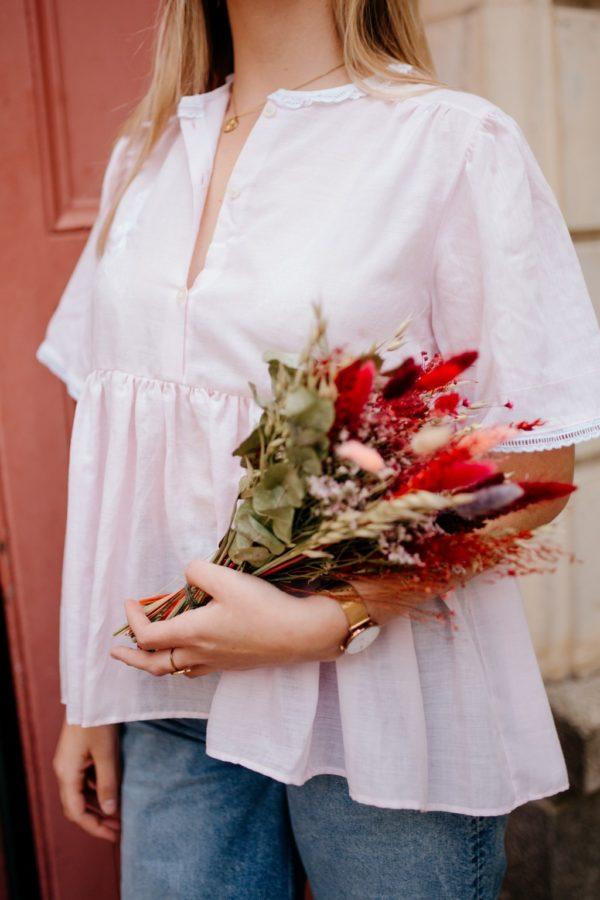 Femme portant une blouse à plis rose upcyclé réalisé par nos couturières avec un bouquet de fleur à la main