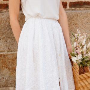 Femme portant une jupe plissée blanche upcyclé réalisé par nos couturières avec des fleures à la main