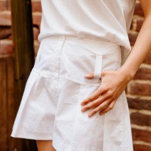 Femme portant un short à plis blanc upcyclé réalisé par nos couturières