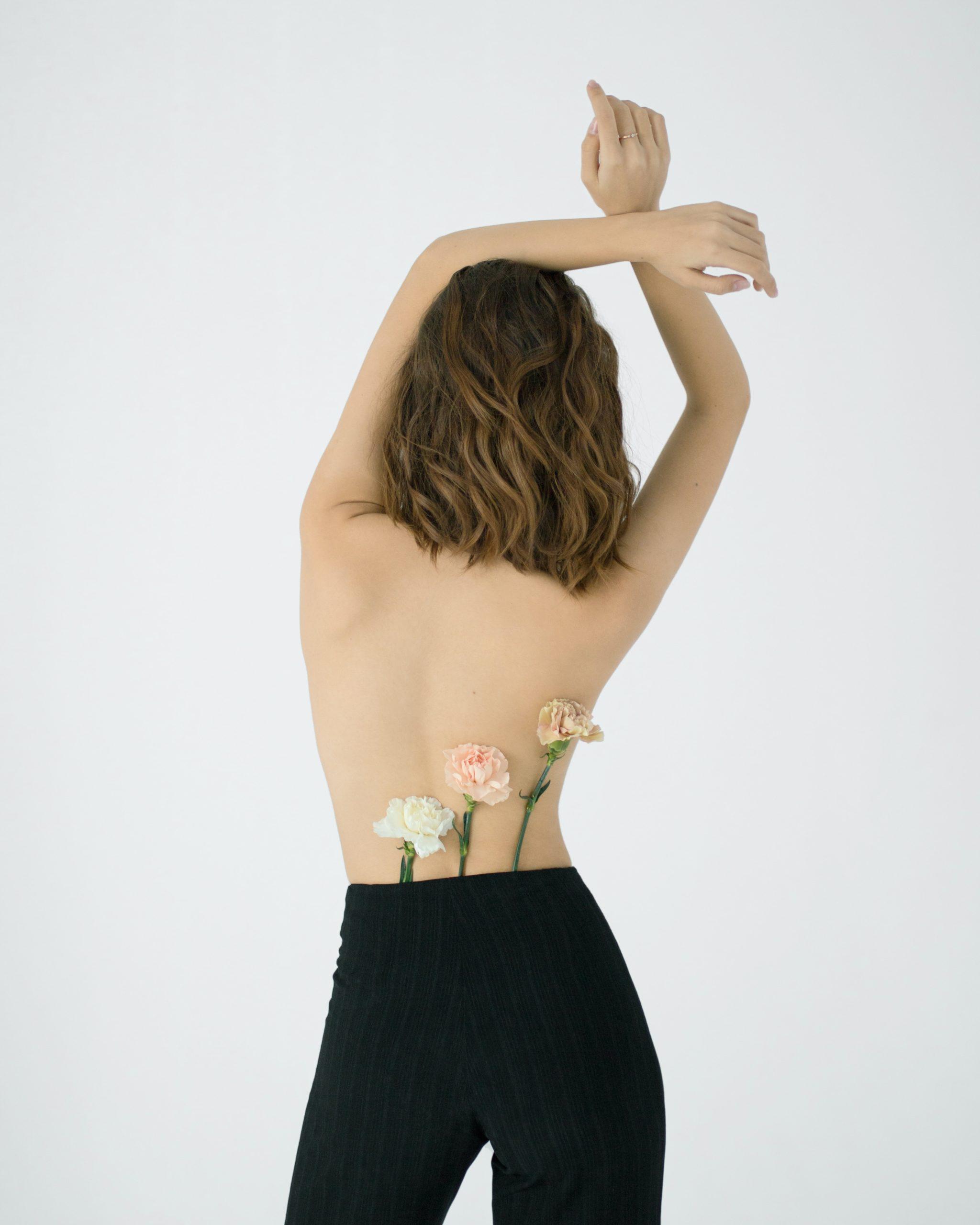 Femme dos nu portant des fleurs synonyme d'écologie afin de comprendre nos différentes morphologies
