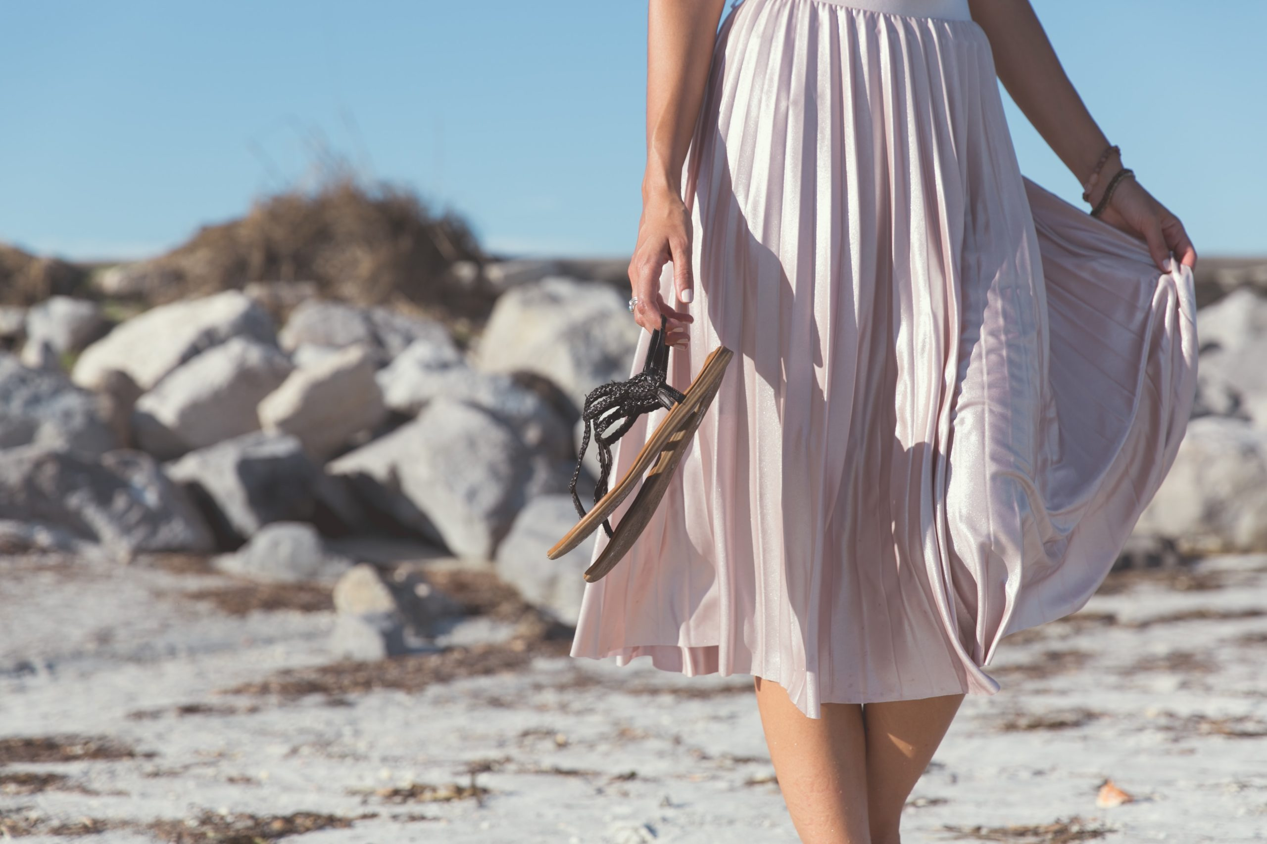 Femme sur la plage en jupe upcyclé portant à sa mains des sandales et montrant une coupe spécifique de jupe