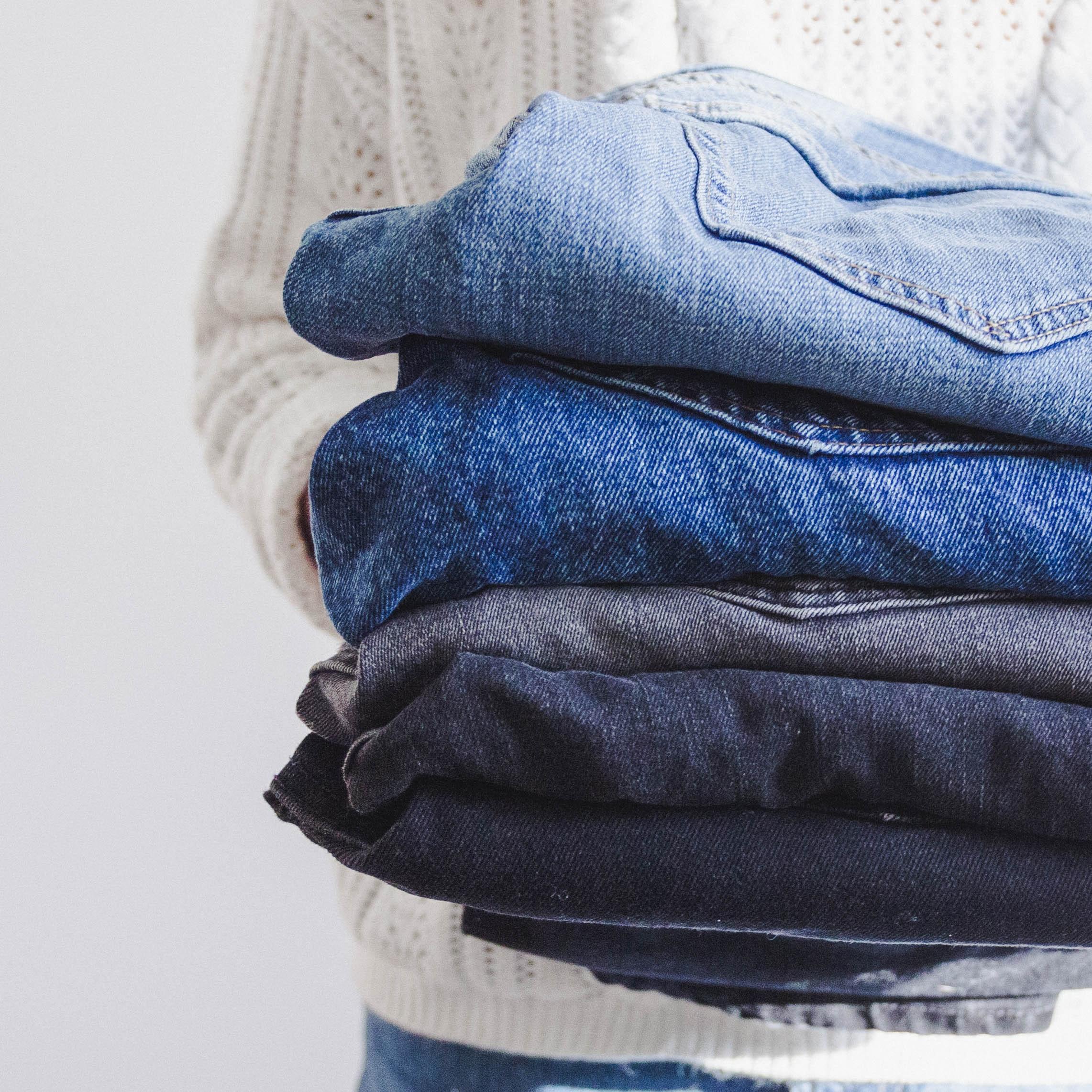 Ensemble de jeans superposés les uns sur les autres de taille, coupe et couleurs différentes