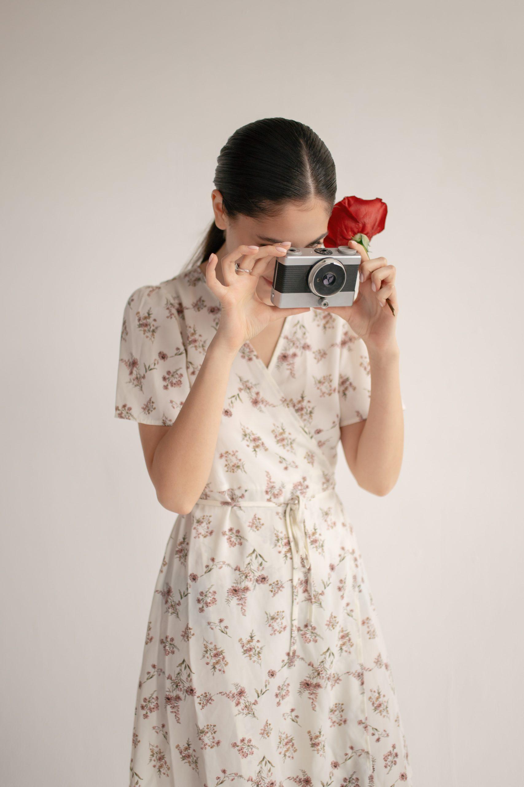 femme tenant un appareil photo et une rose et portant une robe à motif fleuri